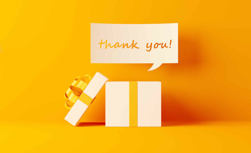 A thank you note coming out of white gift box on yellow background. Horizontal composition with  copy space. Shopping and gift concept.