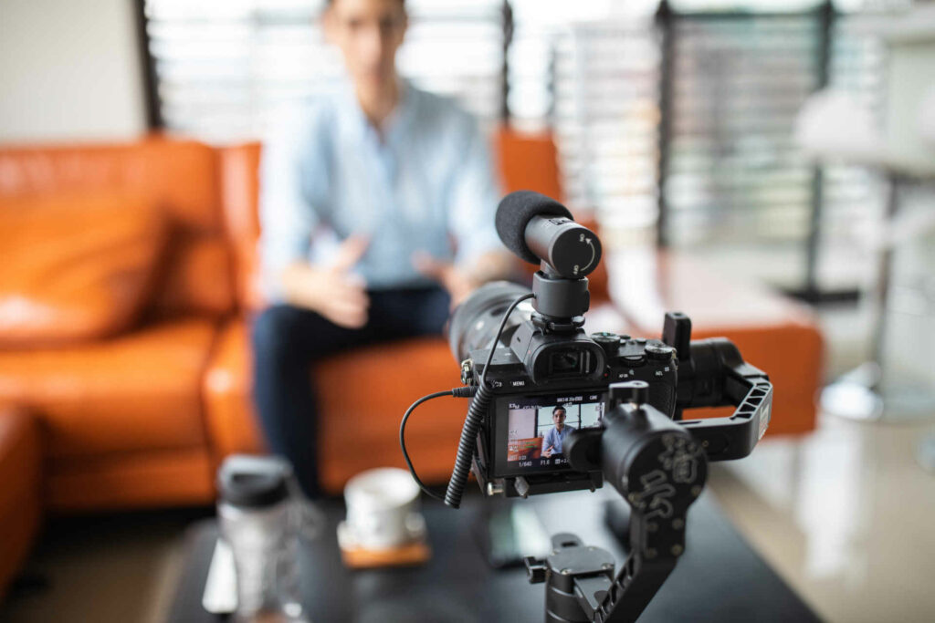 Young handsome man sitting at home on sofa and recording a video with professional camera, looking at camera and talking, focus on foreground